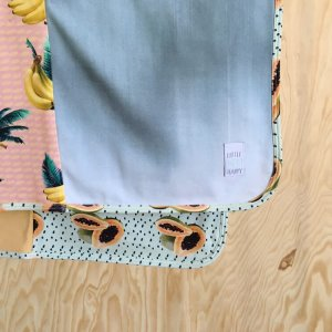 green, orange and yellow baby blanket with bananas and papayas and a grey backside made of organic cotton